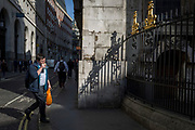 Man eating snack and sunlit railings of St. Mary Woolnoth church on Lombard Street, on 10th May 2017, in the City of London, England.