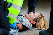 A protestor appears to be crying after Police officers carried her during the group's 'Impossible Rebellion' series of actions at Oxford Circus in central London, on Wednesday, August 25, 2021. - Climate change demonstrators from environmental activist group Extinction Rebellion continued with their latest round of protests in central London, promising two weeks of disruption. (VX Photo/ Vudi Xhymshiti)