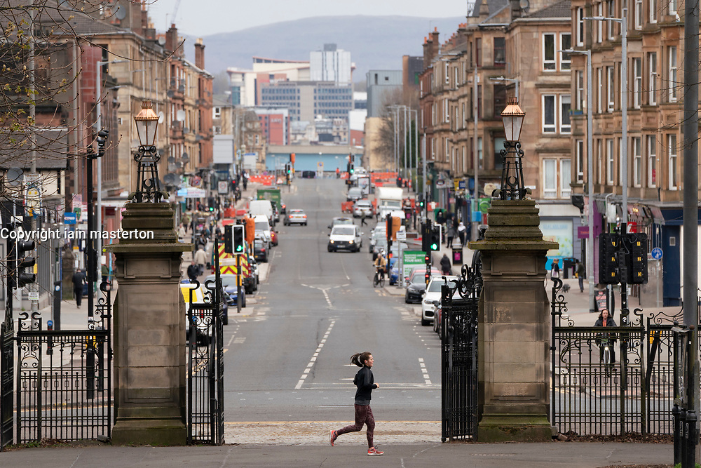 Glasgow, Scotland, UK. 3 April, 2020. Images from the south side of Glasgow at the end of the second week of Coronavirus lockdown.  Jogger runs past a very quiet Victoria Road in Govanhill.  Iain Masterton/Alamy Live News
