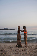 Rio de Janeiro, Brazil - March 9, 2019: A woman from Argentina, visiting Brazil, learns to do a handstand at sunset with the help of her friend on Ipanema Beach in Rio de Janeiro, Brazil.