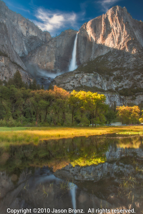 Upper Yosemite Falls reflected in a snowmelt pool in a medow in spring, Yosemite National Park, California.