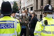 Acting Green Party leader Sian Berry and Green Party London Assembly Member Caroline Russell speak to Metropolitan Police officers operating a cordon around environmental activists from Extinction Rebellion in the Covent Garden area during the first day of Impossible Rebellion protests on 23rd August 2021 in London, United Kingdom. Extinction Rebellion are calling on the UK government to cease all new fossil fuel investment with immediate effect.