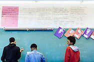 Junior Christopher Higgins (right) works at the chalkboard with other students during their Spanish class at Normandy High School in Wellston, Missouri.