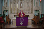 Father Michael Branch delivers mass to parishioners via live-stream at on 27th March 2020 at St Peters Roman Catholic Church in Woolwich, London, United Kingdom. Following the governments advice on social distancing, the Catholic Church has suspended public worship until further notice to help slow the spread of the Coronavirus. Designed by Augustus Pugin in 1841-42 in the style of the Gothic Revival, St Peters RC,  is one of only three Pugin churches in London. In 1883 St Peter the Apostle Roman Catholic Church opened, the first to do so in London, following the Reformation.