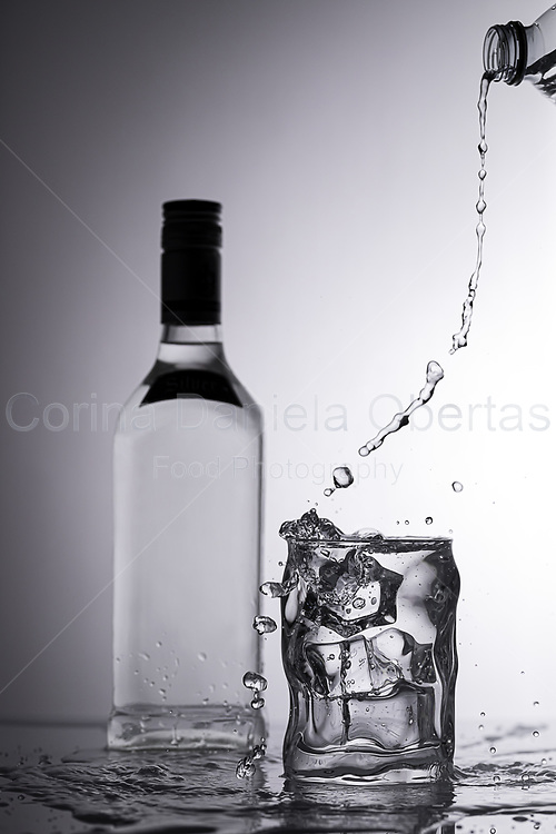 Pouring spirit in a glass with ice cubes - Liquid splash in monochromatic color palette.<br /> EXCLUSIVE ONLY ON THIS SITE!