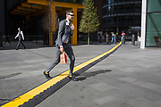 A lunchtime office worker crosses a yellow line covering hazardous electrical cabling at Leadenhall in the City of London, aka The Square Mile the capitals financial district, on 2nd September 2019, in London, England.