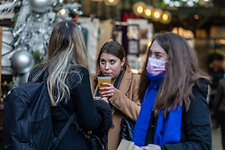© Licensed to London News Pictures. 17/12/2020. London, UK. Beer drinkers enjoy a festive takeaway pint in Covent Garden, London today on the second day of Tier 3 for the capital. Today, Health Secretary Matt Hancock announced the latest updates on the government's tiering system as he plunged more of the South East of England including Surrey and Kent into Covid Tier 3 restrictions after health officials put pressure on the government not to reduce tier levels before Christmas. Yesterday, (Wednesday) London was put into Tier 3 restrictions after a new Covid-19 variant was discovered. Photo credit: Alex Lentati/LNP