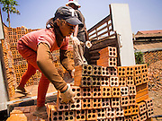 26 FEBRUARY 2015 - PHNOM PENH, CAMBODIA: Workers load bricks onto a delivery truck at a brick making factory on the outskirts of Phnom Penh.    PHOTO BY JACK KURTZ