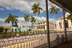 North America, Caribbean, Cuba, Trinidad, Plaza Mayor and palm trees viewed from porch with wrought-iron railing.  Trinidad and the Valley de los Ingenios is a UNESCO World Heritage Site