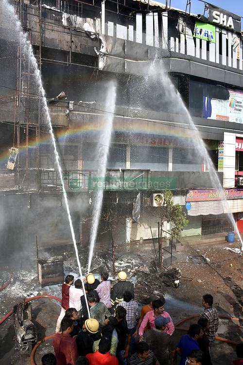 May 24, 2019, Gujara. India: Rescuers work at a building in Surat town of the western Indian state of Gujarat. The death toll in a major fire incident in India's western state of Gujarat has risen to 19, and five injured have been admitted to a hospital, a senior Fire Department official confirmed to Xinhua over phone on Friday. The fire broken out inside a four-storey building in Gujarat's Surat town on Friday afternoon. (Credit Image: © Stringer/Xinhua via ZUMA Wire)