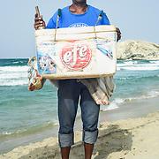 Henry Rafael Marin vende helados Efe hace 23 años en la Playa Parguito. Los precios oscilan entre 80mil y 250mil. Tra consigo 70 u 80 helados y vende en la semana 15 a 20 y los fines de semana 40-50. En temporada alta, vacaciones, vende de 100 a 120 helados. Trabaja de 11am a 4:30pm, 4 dias de la semana porque se turna con el otro compañero. En temporada alta va todos los dias. Nunca se pone protector.