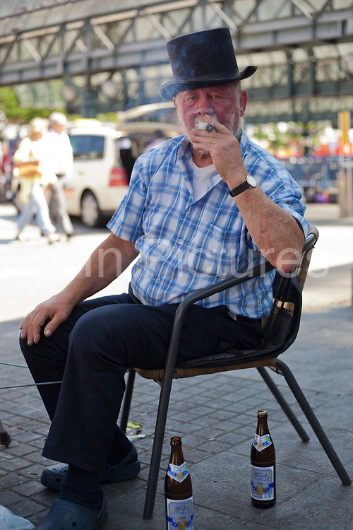 Man smoking cigar Jungfernstieg Central station square, Hamburg, Germany.
