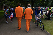 Two Dutch spectators wearing matching orange suits walk along an evenue in the former royal borough of Hampton Court, palace of Henry the Eighth's Hampton Court Palace on the first day of competition of the London 2012 Olympic 250km mens' road race. Starting from central London and passing the capital's famous landmarks before heading out into rural England to the gruelling Box Hill in the county of Surrey. Local southwest Londoners lined the route hoping for British favourite Mark Cavendish to win Team GB first medal but were eventually disappointed when Kazakhstan's Alexandre Vinokourov eventually won gold.