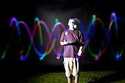 Boy juggling three multi-colored light-up balls.