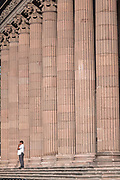A man stands by the massive pink quarry stone columns of the State Government Palace and Museum or Palacio de Gobierno del Estado de Nuevo Leon in the Macroplaza Grand Plaza alongside the Barrio Antiguo neighborhood of Monterrey, Nuevo Leon, Mexico.