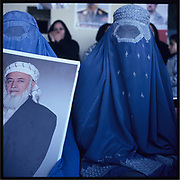 Women clad in burqa holds a portrait of Burhanuddin Rabbani, the former President of Afghanistan of the exiled government during the Taliban rule, during a warlords rally held in Kabul Stadium.