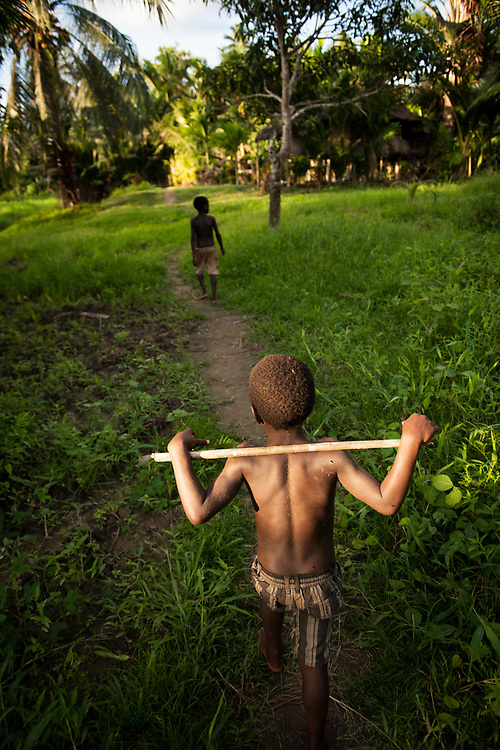 Children walk in the village of Likan, located beside the Clay River in East Sepik Province, Papua New Guinea.<br /><br />(June 2019)