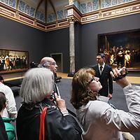 Nederland, Amsterdam , 13 april 2013.<br /> Openingsdag van het Rijksmuseum,<br />  Het publiek mocht gratis een kijkje nemen in het museum dat meer dan 10 jaar gesloten was vanwege renovatie.<br /> Op de foto: Bezoekers wandelen langs de Nachtwacht van Rembrandt.<br /> Amsterdam, 13 April 2013 Rijksmuseum opened after 10 years of renovation: the public could take a look at the museum for free. At Rembrandt's Nightwatch.