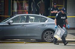 Police investigate a car with a bullet hole within the scene of a shooting in east Toronto, on Monday, July 23, 2018. Police were trying Monday to determine what prompted a 29-year-old man to go on a shooting rampage in a popular Toronto neighbourhood, killing two people and injuring 12 others.THE CANADIAN PRESS/Christopher Katsarov