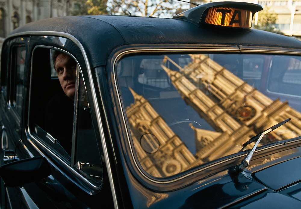 Britain, England.  London Cab with reflection of Westminster Abbey in his window.