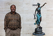 Man waiting outside lawyers office on 5th March 2020 in downtown Dothan, The Peanut Capital of the World, Alabama, United States of America. Lady Justice Latin: Iustitia is an allegorical personification of the moral force in judicial systems. Her attributes are a blindfold, a balance, and a sword. Her balance has disappeared.