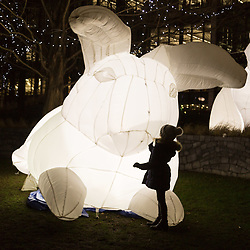 Canary Wharf, London, January 16 2018. A girl admires 'Intrude' - two inflatable white rabbits by Amanda Parer of Australia at the Winter Lights festival at Canary Wharf in London which features over 30 spectacular light installations at interactive art. © Paul Davey