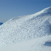A mountaineer stand walks up one of the highesr peaks of Chile's previously unexplored Cordillera Sarmiento, a range beset by furious Patagonian weather coming off of the Pacific Ocean.  The snow textures are wind-blasted rime.
