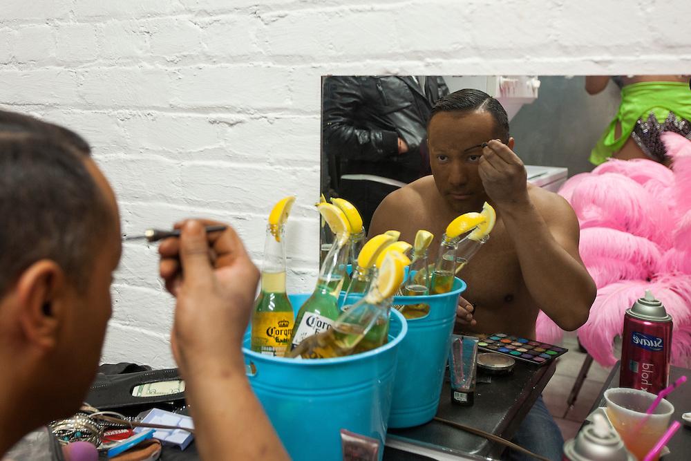 Manolo Gonzales, 34, applies eye makeup backstage.
