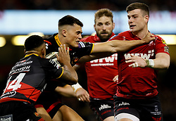 Dragons' Jared Rosser under pressure from Scarlets' Scott Williams<br /> <br /> Photographer Simon King/Replay Images<br /> <br /> Guinness PRO14 Round 21 - Dragons v Scarlets - Saturday 28th April 2018 - Principality Stadium - Cardiff<br /> <br /> World Copyright © Replay Images . All rights reserved. info@replayimages.co.uk - http://replayimages.co.uk