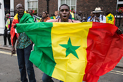 London, UK. 10 July, 2019. Members of the Senegalese community in the UK protest outside Chatham House during an interview by Evan Davis of BP Group Chief Executive Bob Dudley to discuss balancing increasing energy needs  with climate change considerations. The protest followed a BBC Panorama exposé on a $10bn petrol and gas corruption scandal in Senegal for which they hold BP accountable, as well as the awarding of an oil exploitation contract through Timis Corporation.