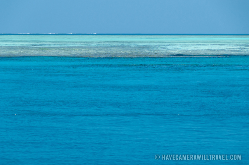 A view of the horizon on the Great Barrier Reef, Australia. The blue water in the bottom part of the frame is deeper water with a mostly sandy bottom. Beyond that, the darker area is a mix of shallow reef and sand just below the surface of the water. The shallow reef provides a natural barrier against waves and swells. This particular shot was taken about 150 miles northeast of Gladstone on Swains Reef, about 115 miles offshore.