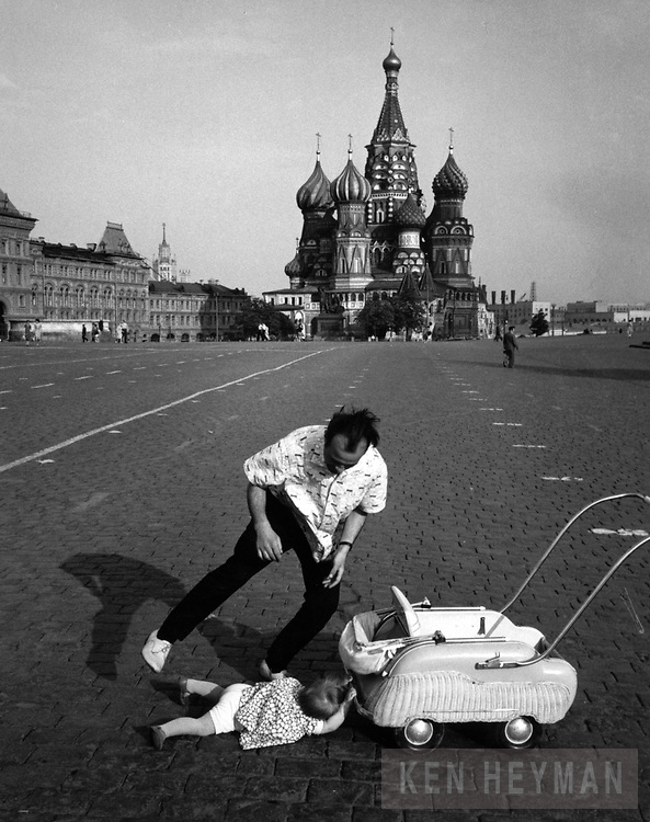 In Moscow's Red Square, a father is about to pick up his child that fell down while pushing the carriage.