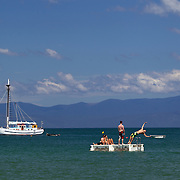 Boats on the water as people play on a pontoon near Kaiteriteri, a beautiful seaside resort town in the Nelson region, set close to the Abel Tasman National Park, New Zealand, 3rd February 2011. Photo Tim Clayton