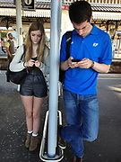 Two young people texting from the mobile phone devices while standing at a railway station platform. These two seperate people are lost in their world of communication via text. London, UK.