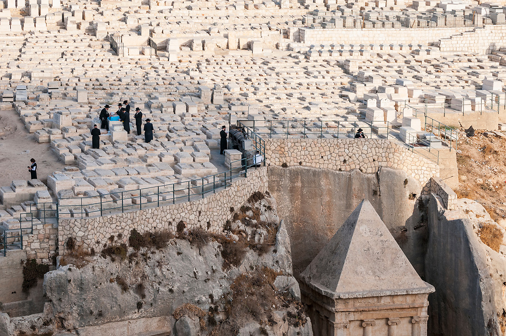 Several Jewish men stand around a grave above the Tomb of Zechariah ben Jehoiada in Jerusalem. The monumental rock-cut tomb is located in Jerusalem's Kidron Valley, a few meters from the Tomb of Absalom. Photo taken on October 20, 2010.