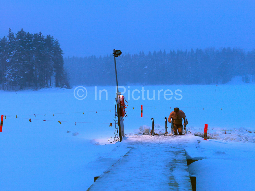 After a brief dip, a man gets out the hole cut into a frozen lake for ice-swimming, Kallavesi, Kuopio, Central Finland. Ice swimming takes place in a body of water with a frozen crust of ice, which requires a hole cutting in it.  In Finland, the ice swimming tradition has generally been connected with the sauna tradition and it is not seen as an ascetic or religious ritual, but as a way to cool off rapidly after staying in the sauna and as a stress relief.