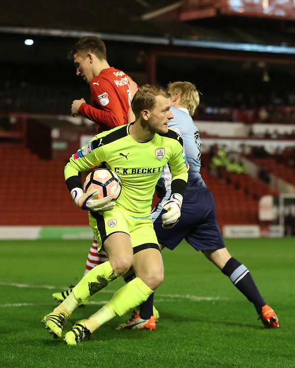 Blackpool's Mark Cullen fights for the ball against Barnsley's Angus MacDonald as Barnsley's Adam Davies scoops the ball<br /> <br /> Photographer Rachel Holborn/CameraSport<br /> <br /> Emirates FA Cup Third Round Replay - Barnsley v Blackpool - Tuesday 17th January 2017 - Oakwell Stadium - Barnsley<br />  <br /> World Copyright © 2017 CameraSport. All rights reserved. 43 Linden Ave. Countesthorpe. Leicester. England. LE8 5PG - Tel: +44 (0) 116 277 4147 - admin@camerasport.com - www.camerasport.com