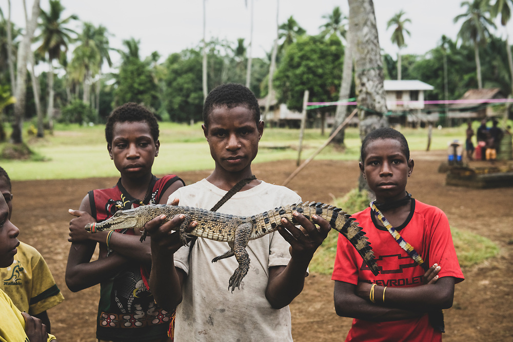 A teenager displays a crocodile caught overnight in Likan, Papua New Guinea.<br /><br />(June 21, 2019)