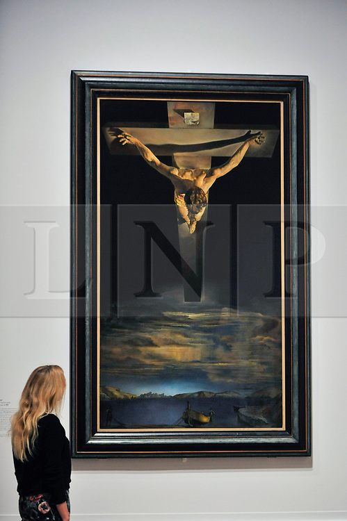 "© Licensed to London News Pictures. 03/10/2017. London, UK.  A staff member views ""Christ of Saint John of the Cross"", 1951, by Salvador Dali at the preview of ""Dali / Duchamp"", a new exhibition of works by Salvador Dali and Michel Duchamp taking place at the Royal Academy of Arts in Piccadilly.  Over 80 artworks in different media are on display from 7 October to 3 January 2018.   Photo credit : Stephen Chung/LNP"