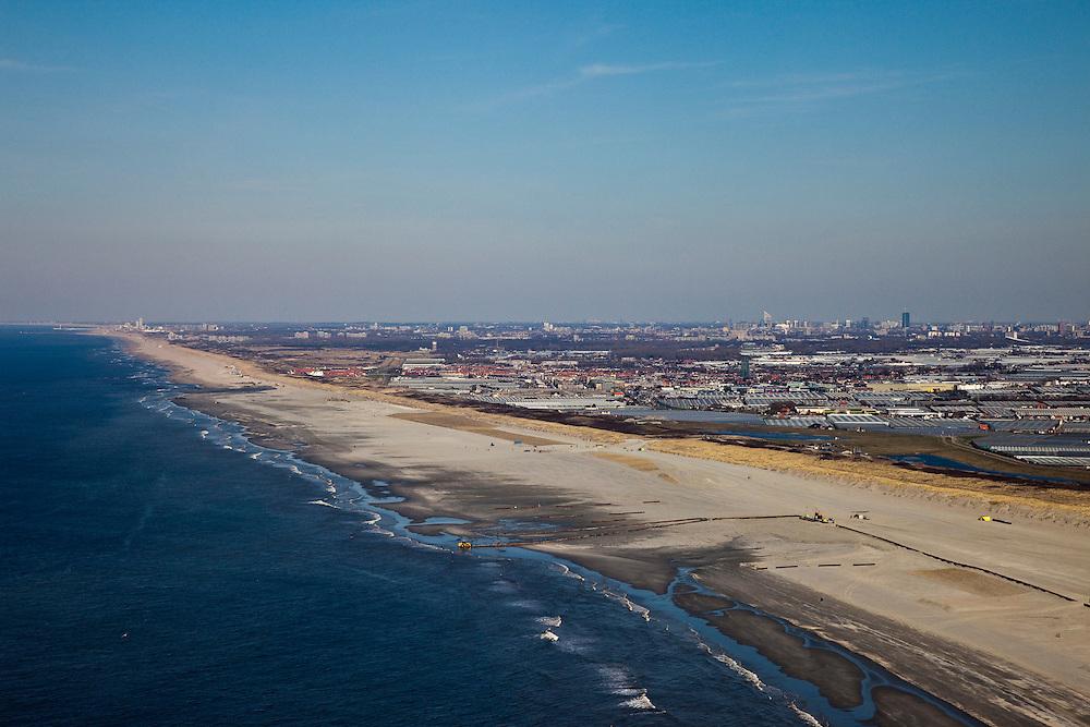 Nederland, Zuid-Holland, Monster, 18-03-2009; Versterking van de kust van Delfland tussen Ter Heijde en 's-Gravenzande door middel van zandsuppletie. Het strand onder in beeld is breder, hier is al gesuppleerd, de zandpersleidingen liggen nog op het strand. Meer naar links, richting Scheveningen moet er nog zand opgespoten worden, bij de donkere plek is suppletie in volle gang. De Delflandse kust is bekend als een van de 'zwakke schakels'.  Achter de duinen de kassen van het Westland, aan de verre horizon de skyline van Den Haag. .The coast of Delfland, between Hoek van Holland and The Hague, is being strengthened by means of sand-supplementation. The beach in the lower part of the picture is wider, sand has already been supplemented, the high pressure pies are still on the beach. Further to the left, sand still needs to be sprayed onto the beach, around the dark area sand-supplementation is in progress. This coast is one of the so-called 'weak-links' because of the weakness of the dunes. At the horizon the skyline of The Hague..Swart collectie, luchtfoto (toeslag); Swart Collection, aerial photo (additional fee required); .foto Siebe Swart / photo Siebe Swart