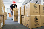 """Stop Hunger Now Foundation program manager Christopher Romero stacks boxes of sealed food packages with the help of more than 300 SanDisk employees during the Stop Hunger Now Foundation's """"Mayday, Mayday"""" food-packing event at SanDisk Corporation in Milpitas, California, on May 13, 2014. (Stan Olszewski/SOSKIphoto)"""