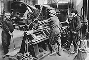 World War I 1914-1918: Women in a German state munitions factory working at a 125 ton grooving press.