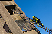 London Fire Brigade, station training session on the second floor of the tower. A firefighter proceeds up the ladder.