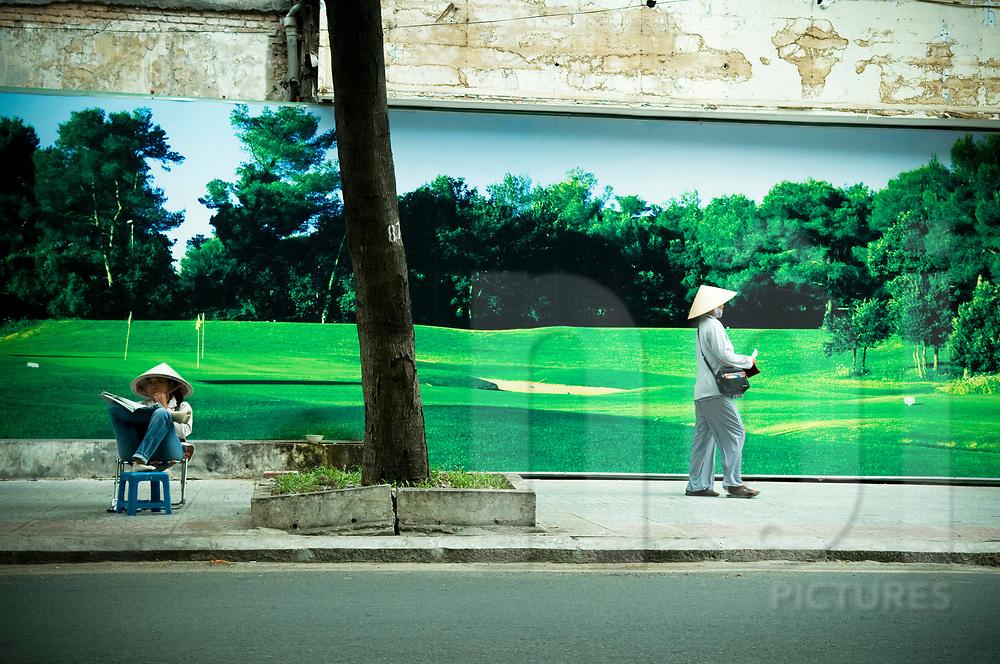 Vietnamese women in front of a trompe-l'oeil billboard in a street of Ho Chi Minh City, Vietnam, Southeast Asia