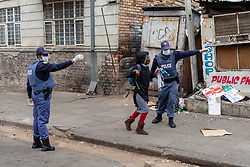 JOHANNESBURG, April 1, 2020  Policemen persuade a citizen to go home in Johannesburg, South Africa, March 30, 2020. South African President Cyril Ramaphosa on Monday defended the 21-day national lockdown against the coronavirus pandemic which began on midnight Thursday, saying it is ''absolutely necessary.'' (Photo by Yeshiel PanchiaXinhua) (Credit Image: © Xinhua via ZUMA Wire)