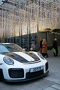 Fairy lights create a raining light type scene outside the exclisive Berkley Hotel in London, United Kingdom. Outside a white and black Porsche supercar is parked. The Berkeley is a five star deluxe hotel located in Knightsbridge. It is managed by the Maybourne Hotel Group.
