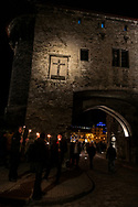 Tallinn, Estonia - February 24, 2020: Stragglers in a march stand at the Great Coastal Gate (Suur Rannavärav) in Tallinn, Estonia. Several thousand Estonians holding tiki torches had just passed through the gate as they marched in support of the Conservative People's Party.