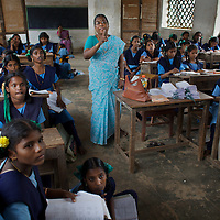 """Staff and pupils at the Government Girls High School, Venugopalapuram, Cuddalore...Cuddalore's Government Girls High School is under-resourced with some student forced to sit on the floor for want of a desk. Though most classrooms are housed in a building that is only two years old, there is little ventilation to lessen the effects Cuddalore's tropical heat. The school does offer extra """"`bridge"""" classes for those students recently arrived from village schools but staff are frequently absent from the school...Photo: Tom Pietrasik.Cuddalore town, Tamil Nadu. India.October 5th 2009"""