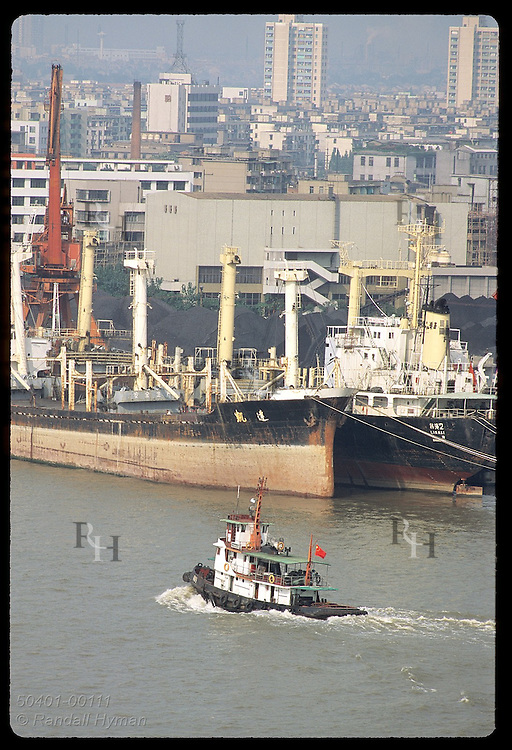 Tugboat chugs past ocean freighters docked at coalyard on banks of Huangpu River; (v) Shanghai China