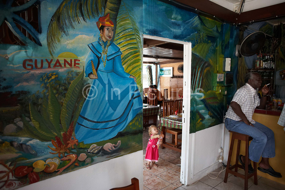 Holding her doll, a young white child wearing a pink dress explores the Délice Restaurant in old Kourou, French Guiana, South America. The daughter of French parents who are in this French-administered colony in connection with the nearby European Space Agency (ESA). The girl is confident enough to leave her parents' side and appear in an open doorway. On the other side of the wall is a giant brightly-painted mural depicting a more traditional side of life in this tropical country. The word Guyane is the French name for Guiana. A female in national costume stands near a palm tree, local produce and vegetation. Meanwhile a dark-skinned Creole man sits on a stool smoking a cigarette chatting to unseen friends - a barfly occupying his usual lunchtime seat. It is a scene of internationalism, cross-culture and youth versus old age.
